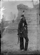 Sioux brave in costume, rock background