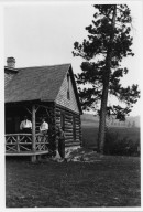 3 unidentified men on porch of log cabin