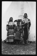 Man, woman and girl outside tipi