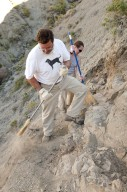 L-R: Dr. Kirk Johnson and a DMNS Volunteer sweep dirt away from an excavation site.