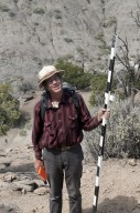 Dr. Bob Raynolds, DMNS Research Associate, holds a survey pole in one hand and his field journal in the other as he looks up at their most recent find.
