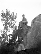 Three boys pose on a rock formation in the mountains.