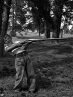 Boy attempts to hold a flintlock rifle.