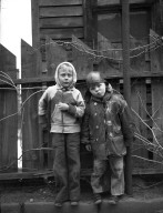 Two unidentified boys pose by a fence.