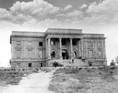 View of man standing by automobile with two people climbing steps up to the Colorado Museum building in 1910.