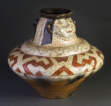 Painted Shipibo jar with faces.