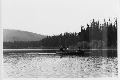 Unidentified man and woman in canoe