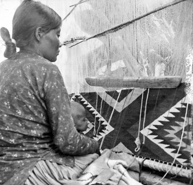 Apache woman and child at loom.