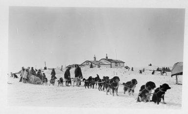 Group of men around loaded dog sled