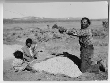 Jicarilla Apache man winnowing grain
