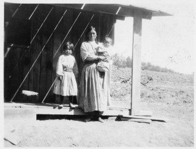 Mrs. Jack Muniz and children on porch.