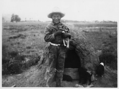 Oliver Levato holding a puppy in front of an earth oven.