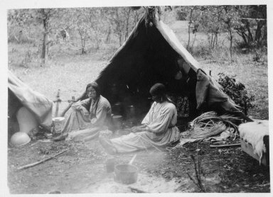 Basketmaking: Christina Jones and Lelia's mother, Leason Garcia Velarde, in modern dress, seated in front of tent.