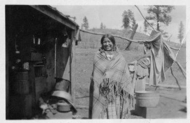 Mrs. Inez No Tongue wearing a shawl standing outside frame shelter.