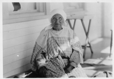 John Bill's mother in an old style cotton dress.