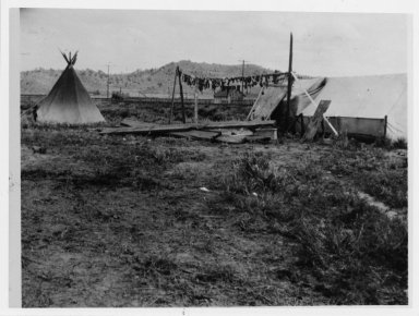 Camp scene showing tipi, tent and drying meat