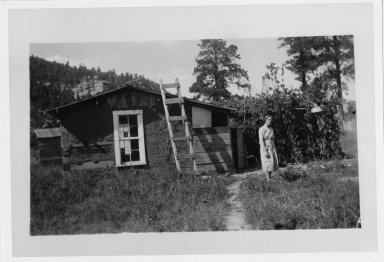 Hendrina Hospers outside timber house mudded with adobe for insulation; brush shelter at side