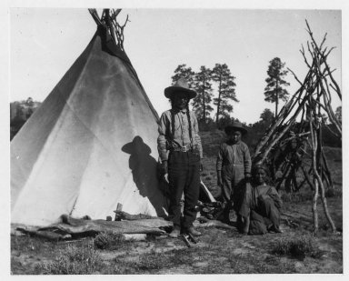 Camp: Man, woman (old style dress), boy (wearing school type outfit), tipi