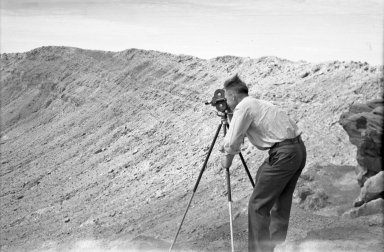 Alfred M. Bailey with movie camera on crater rim
