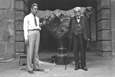 2 men posing with Meteorite on pedestal