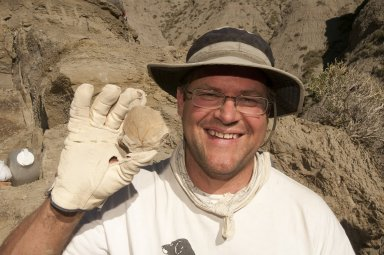 Dr. Kirk Johnson holds up a newly discovered leaf specimen.