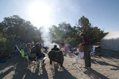Dr. Bob Raynolds, DMNS Research Associate, conducts a morning briefing around the camp fire while the group takes notes.