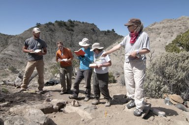 The students in the DMNS Paleontology Field School take notes and ask questions of Dr. Joseph Sertich at the most recent find.