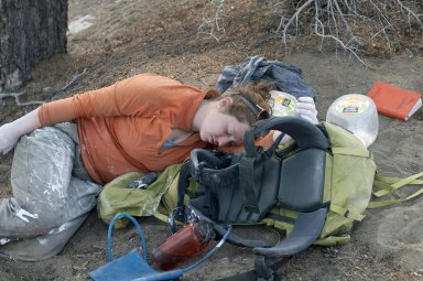 Gussie McCracken, DMNS Staff, rests on her pack after a long day of preparing field jackets for fossils. Note the plaster still on her hands.