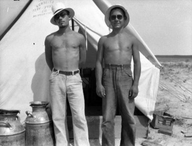 Two unidentified field workers in front of tent