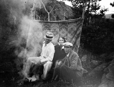Robert Landberg (L) and friends cook over an open fire in the mountains.