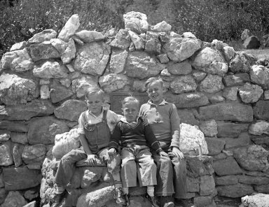 Three boys pose in front of a plaque in the mountains.