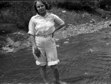 Young woman standing in a mountain stream.
