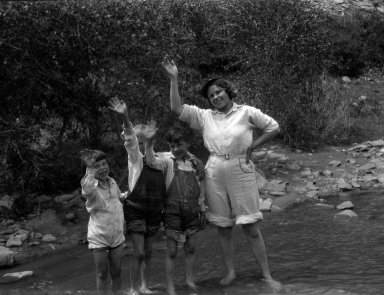 Young woman standing in a mountain stream along with three children.