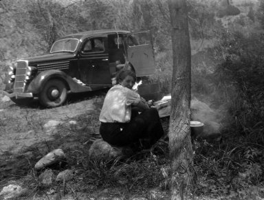 Young woman cooks at the camp site.