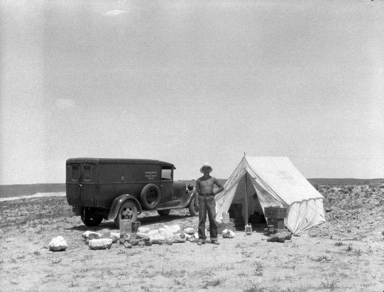 Field worker beside tent and field truck