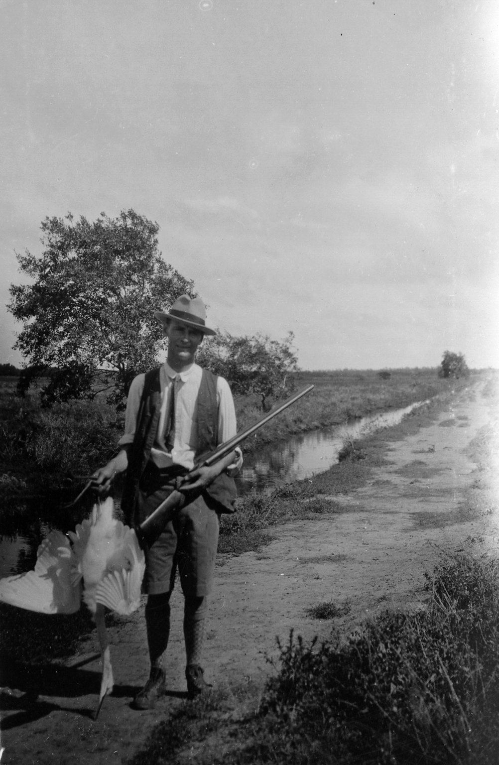 Frederic Walter Miller holding a gun and a wood ibis at at Berheice