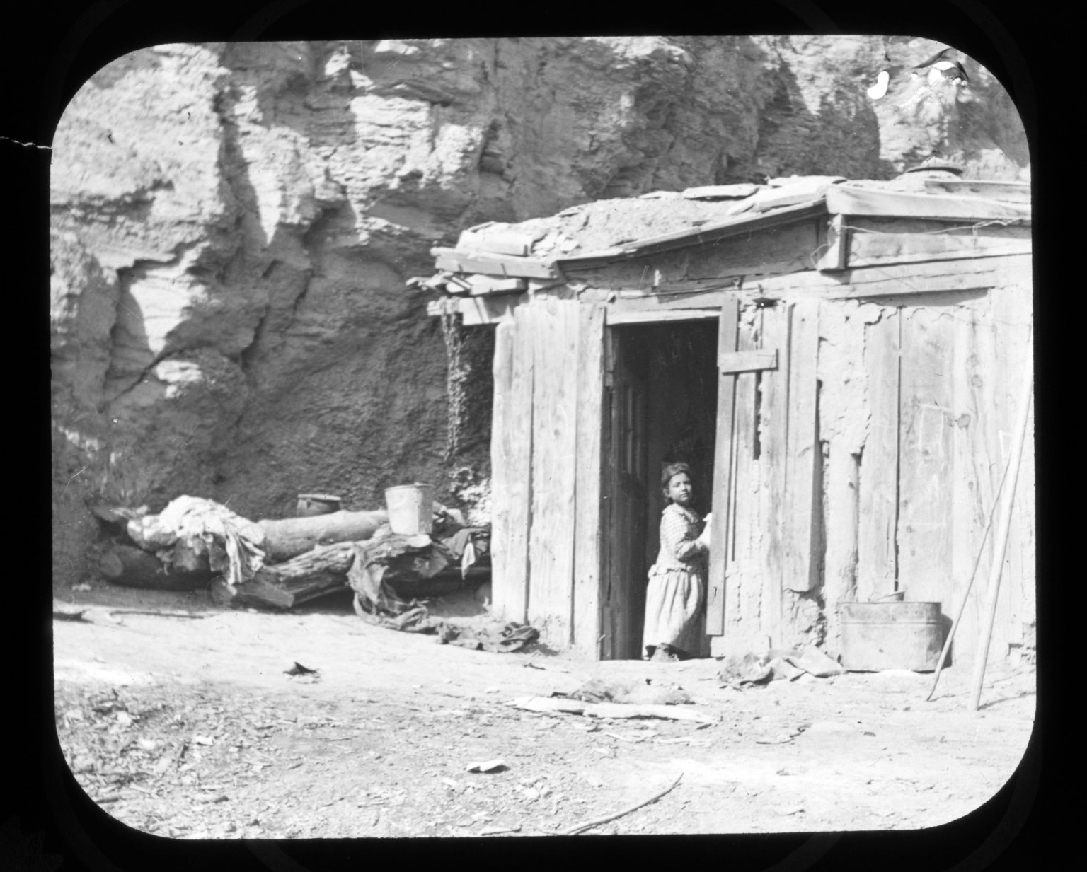 Little girl at the door of a shack.
