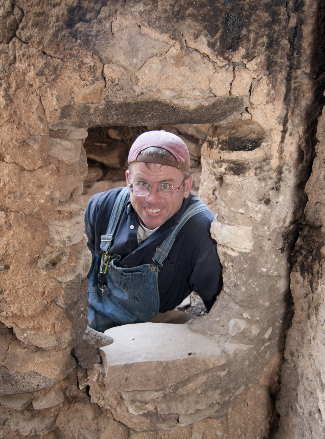 Dr. Steve Nash peers through a door at the Hinkle Park Cliff Dwelling research site.