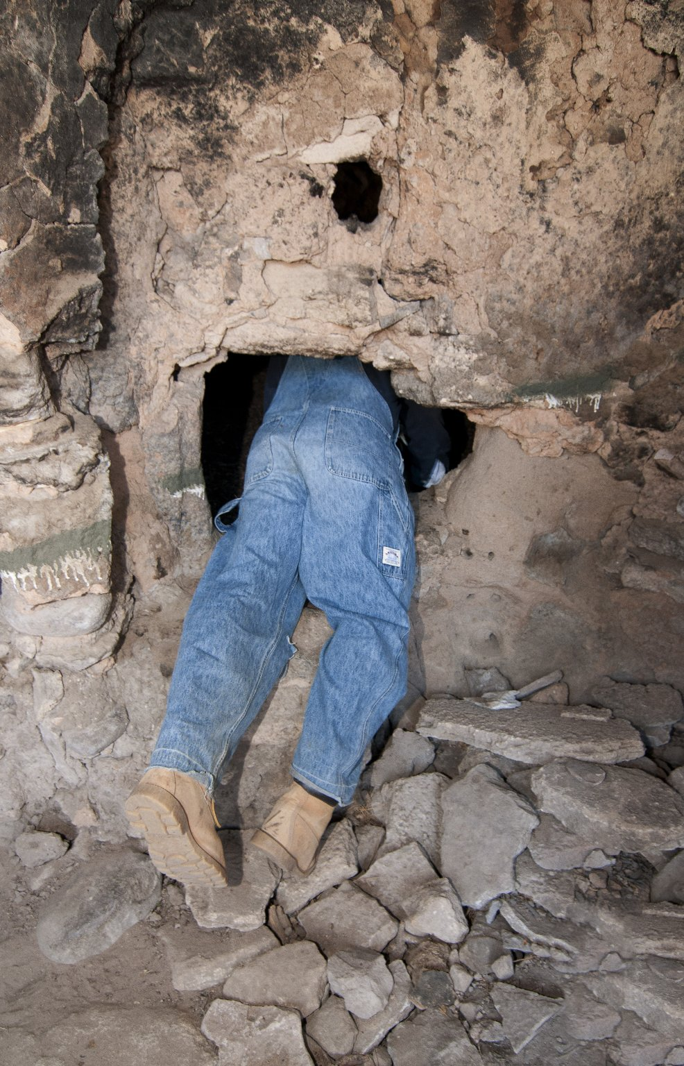 Dr. Steve Nash crawls through a door at the Hinkle Park Cliff dwelling research site.