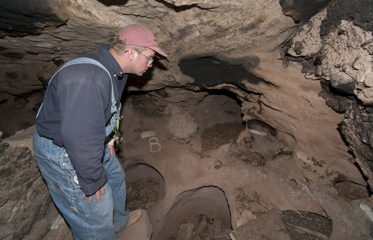 Dr.Steve Nash looks at the back wall at the Hinkle Park Cliff Dwelling site.