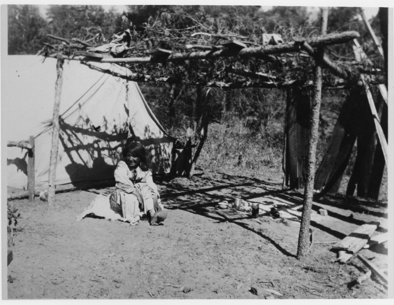 Camp scene showing tent with adjacent ramada.