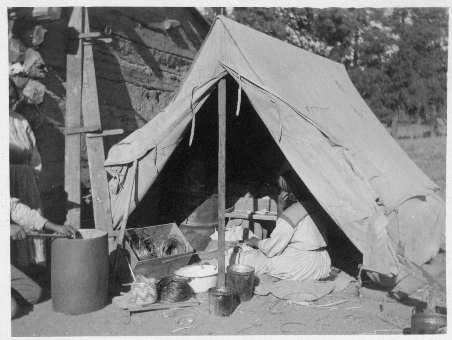 Tent next to log house, basketmaking in progress.