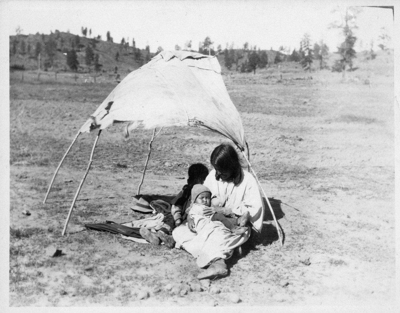 Woman nursing baby under pole and cloth shelter.