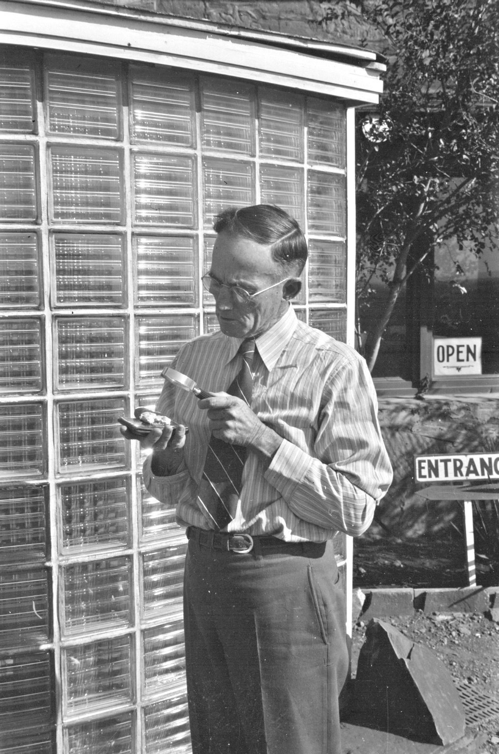 H.H. Nininger examining fragments of the Norton County, Kansas meteorite with magnifying glass at the American Meteorite Museum near Winslow, Arizona.