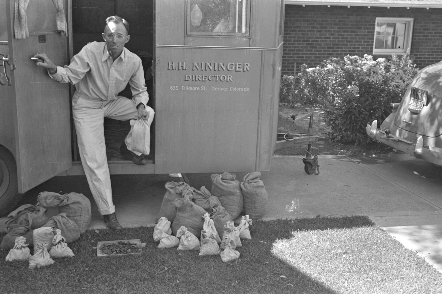 H.H. Nininger in American Meteorite Laboratory with specimen bags in what apears to be the driveway of his house