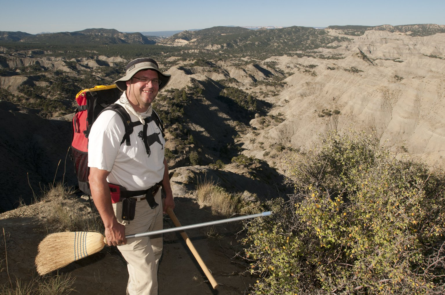 Dr. Kirk Johnson poses holding his tools with the Kaiparowits Plateau in the background.