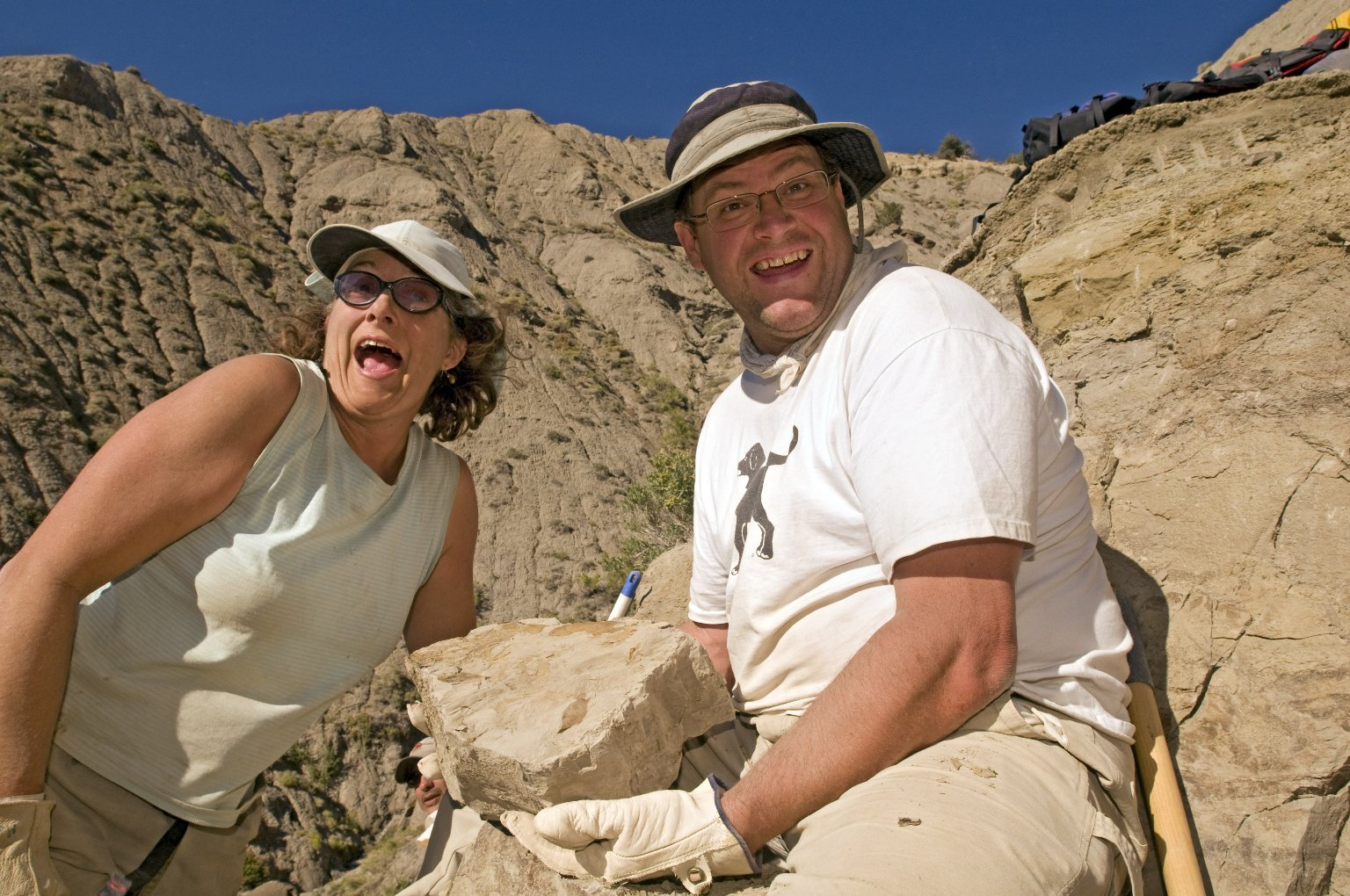 L-R: DMNS Volunteer Cheryl McCutchen and Dr. Kirk Johnson show a specimen at a dig site.