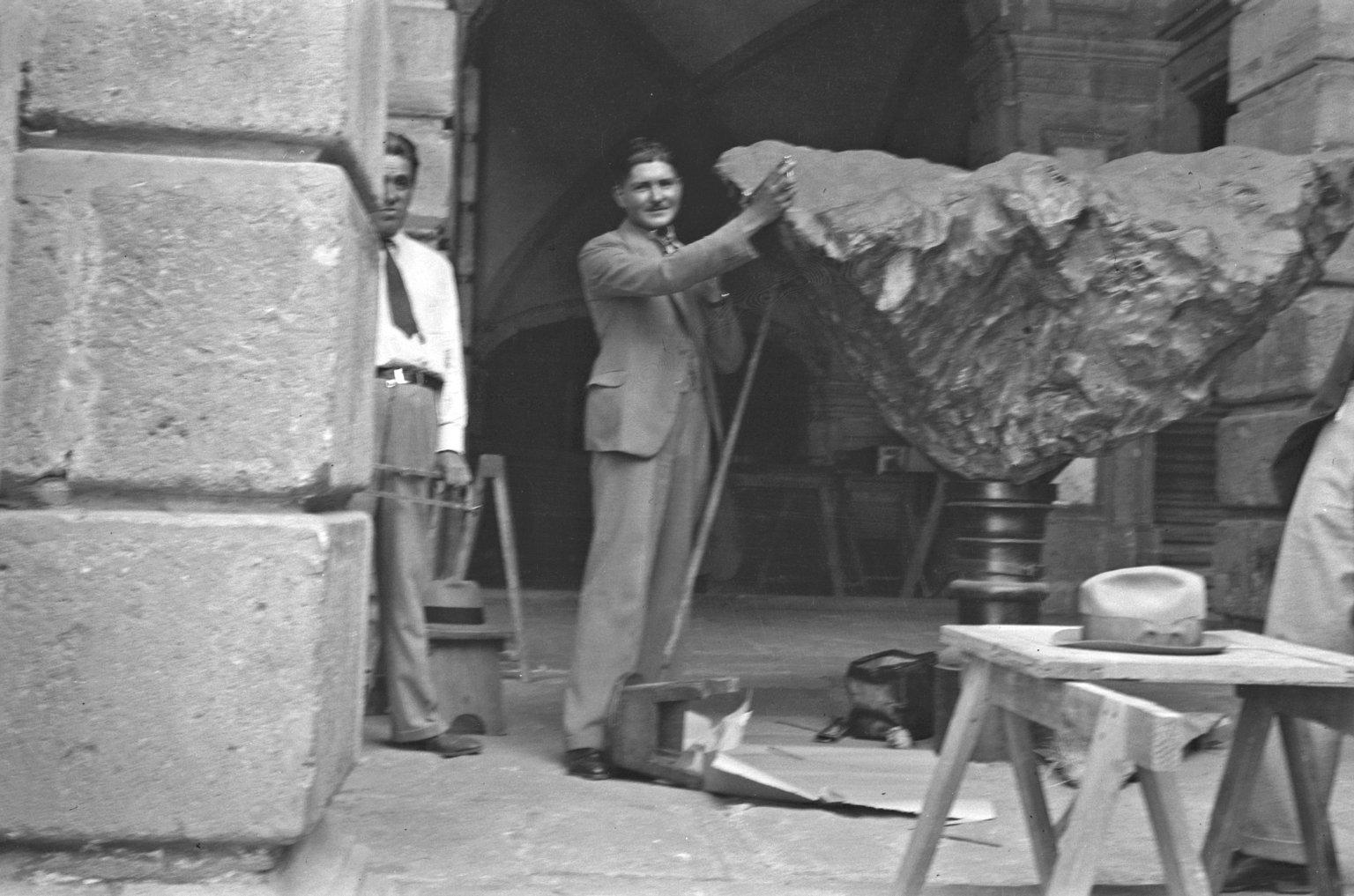 Museum workers posing with Meteorite on pedestal