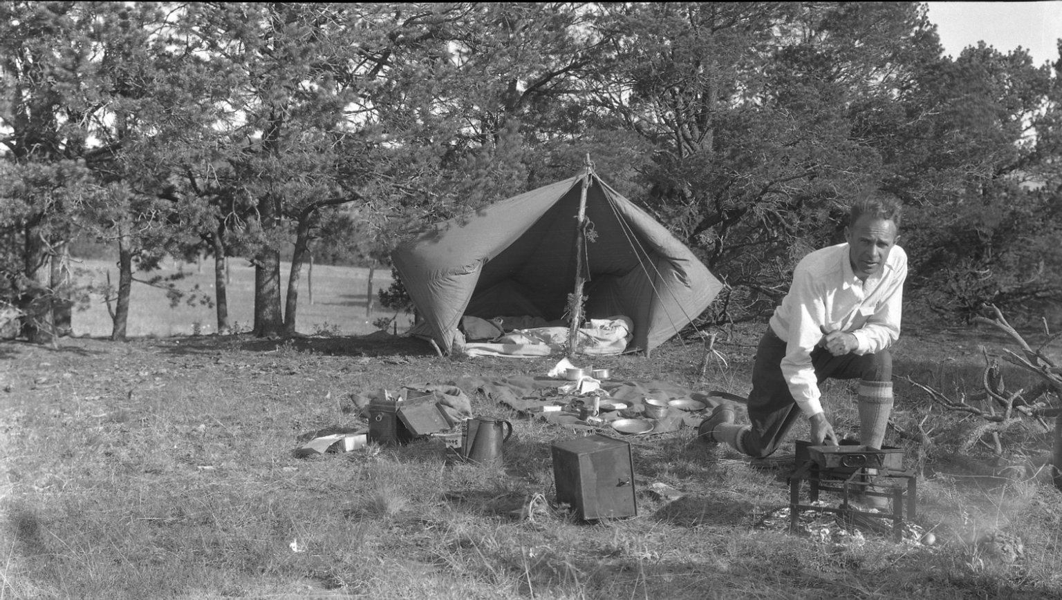 R.J. Niedrach cooking over campfire