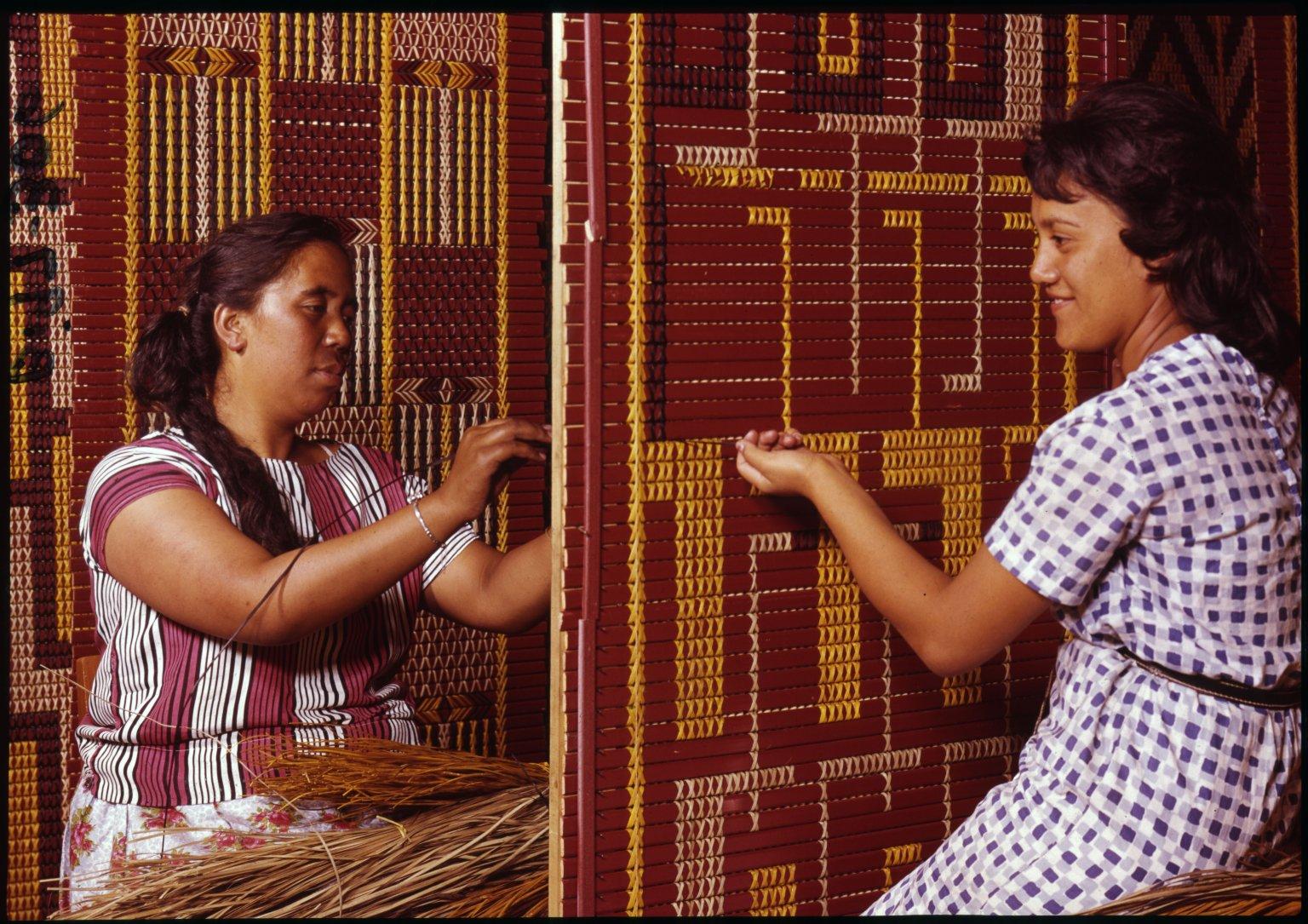 Maori women working on tuku tuku panelling.